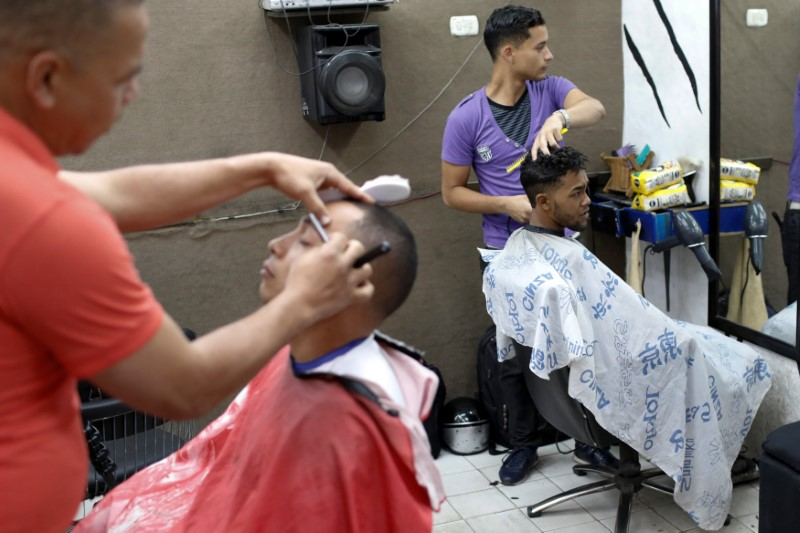 A man gets a haircut after paying for it with two packages of corn flour in Caracas, Venezuela