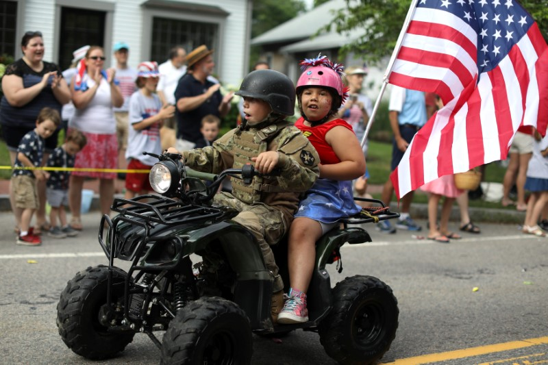 Two children ride on a mini all terrain vehicle down Main Street during the annual Fourth of July parade in Barnstable Village