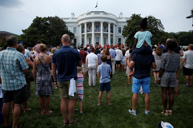 People stand during the National Anthem at a picnic for military families celebrating Independence Day at the White House in Washington