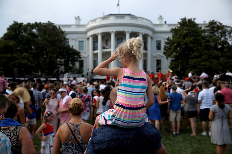 A girl wipes her face as she awaits the arrival of U.S. President Donald Trump and U.S. first lady Melania Trump at a picnic for military families celebrating Independence Day at the White House in Washington