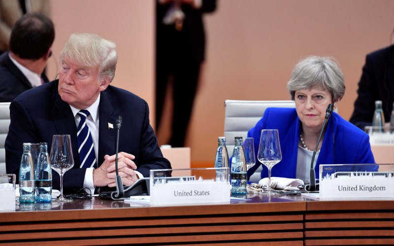 U.S. President Donald Trump and Britain's Prime Minister Theresa May wait at the start of the first working session of the G20 meeting in Hamburg