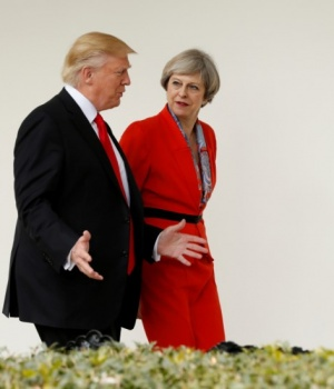 U.S. President Donald Trump escorts British Prime Minister Theresa May down the White House colonnade after their meeting at the White House in Washington