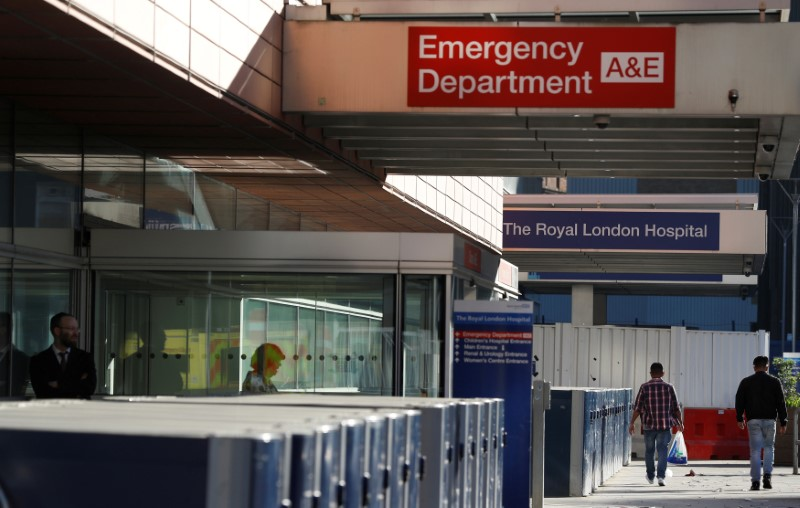 People walk away from the emergency department of the Royal London Hospital, in London