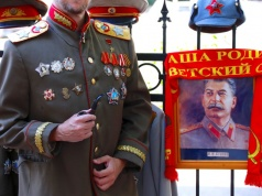 A tourist, visiting Russia during the Soccer World Cup, poses for a photograph dressed in a Russian military costume outside the entrance to Stalin's Bunker in Samara