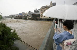 A kimono-clad woman using a smartphone takes photos of swollen Kamo River caused by a heavy rain from Shijo Bridge in Kyoto