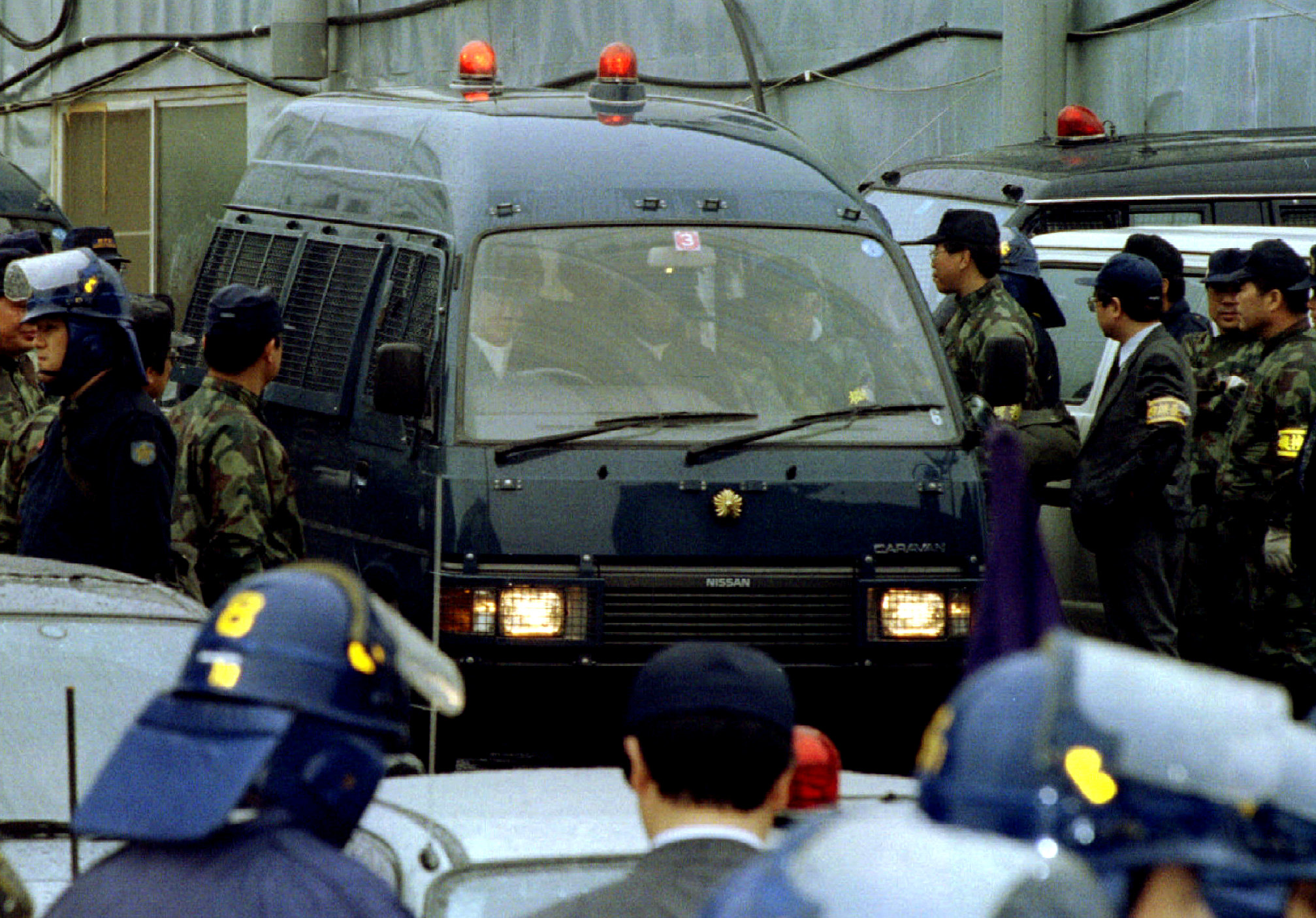 A police vehicle transporting Aum Shinri Kyo sect guru Shoko Asahara is surrounded by policemen as the doomsday prophet is arrested at the cult's Kamikuishiki compounds