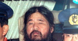 Japanese doomsday cult leader Shoko Asahara sits in a police van following an interrogation in Tokyo