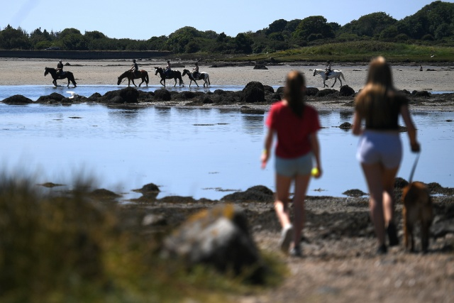 Women view horses as they bring a dog for a walk on Rusheen beach during sunny weather in Galway