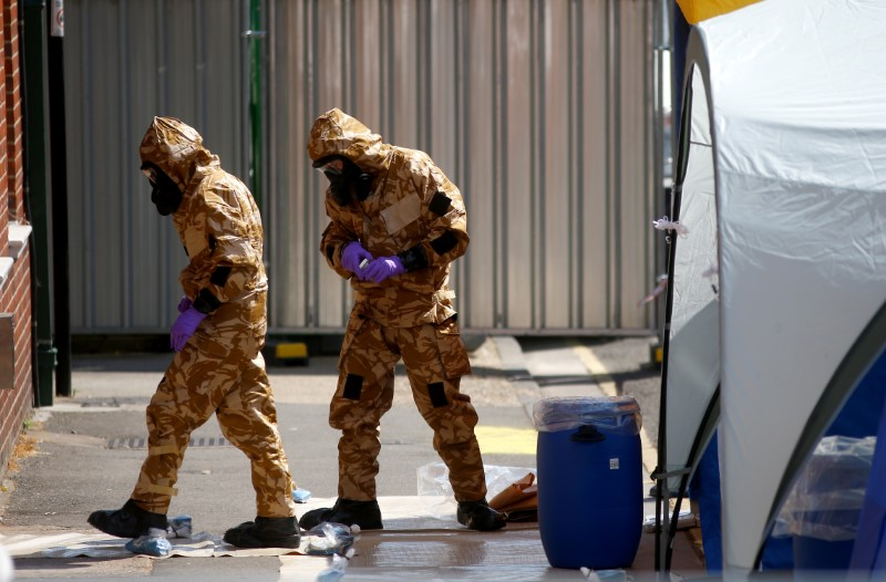 Forensic investigators wearing protective suits enter the rear of John Baker House, after it was confirmed that two people had been poisoned with the nerve-agent Novichok, in Amesbury