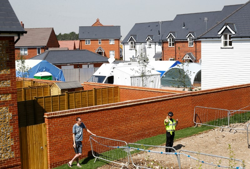 A police officer stands guard behind a housing estate on Muggleton Road, after it was confirmed that two people had been poisoned with the nerve-agent Novichok, in Amesbury