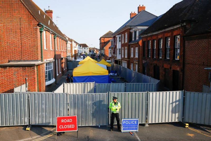 A police officer stands in front of screening erected behind John Baker House as forensic tents are erected, after it was confirmed that two people had been poisoned with the nerve-agent Novichok, in Amesbury