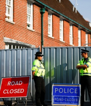 Police officers stand in front of screening erected behind John Baker House, after it was confirmed that two people had been poisoned with the nerve-agent Novichok, in Amesbury
