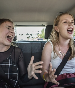 Natalie Pekonen and Salli Degerman sing while riding the 'Singalong Shuttle Cab' to Ruisrock festival area in Turku