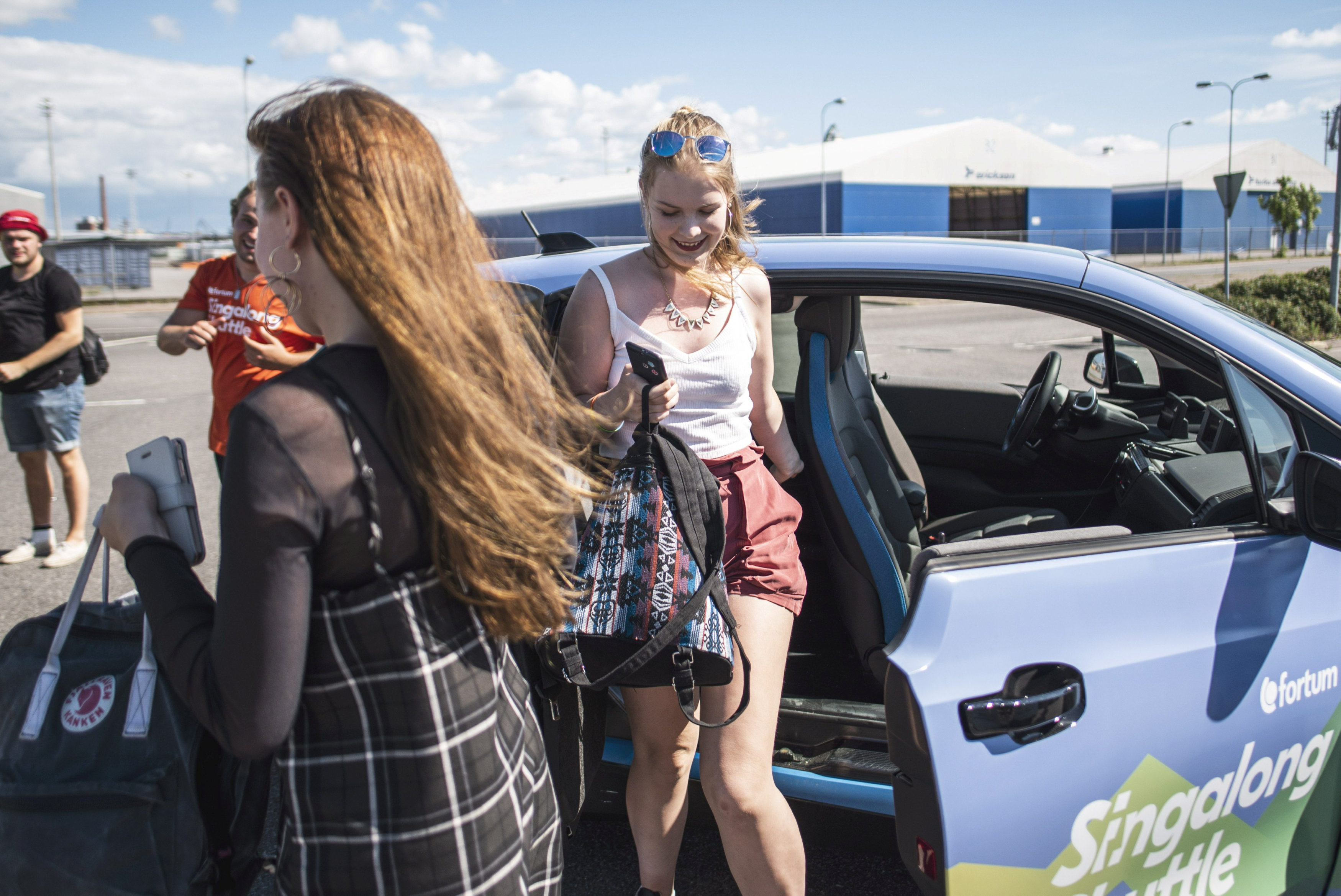 Natalie Pekonen and Salli Degerman get out of the 'Singalong Shuttle Cab' after arriving to Ruisrock festival area in Turku