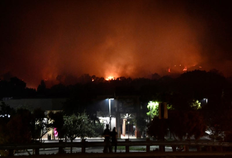 People watch as fast-moving wildfire burns in Goleta