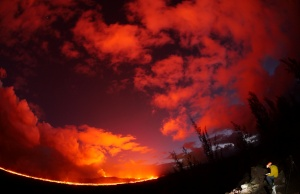 A USGS geologist making observations of the fissure 8 lava channel at sunset is pictured in this fisheye lens handout photograph near the Kilauea volcano eruption