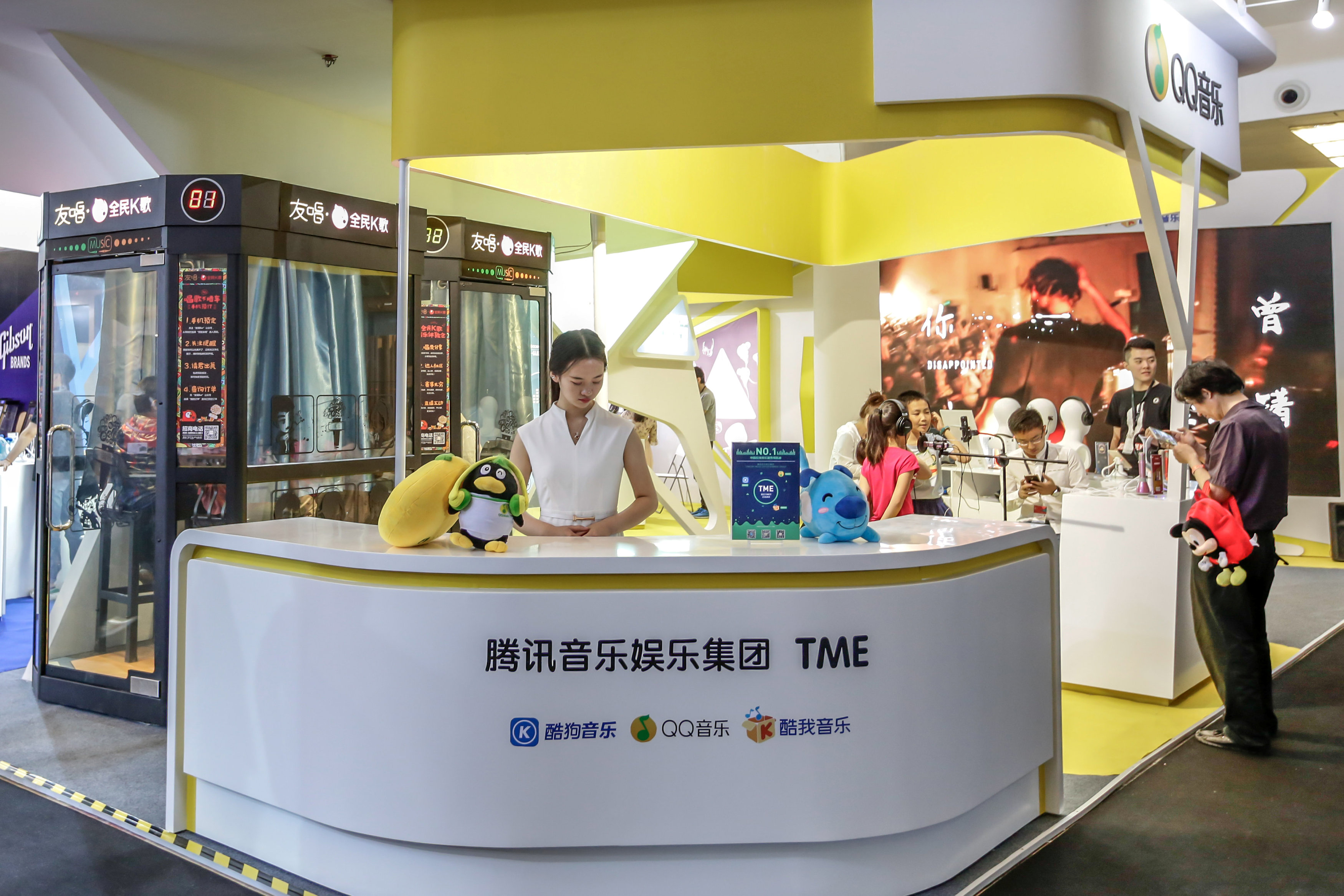 Visitors are seen at a booth of Tencent Music Entertainment at the Beijing Music and Life Show in Beijing