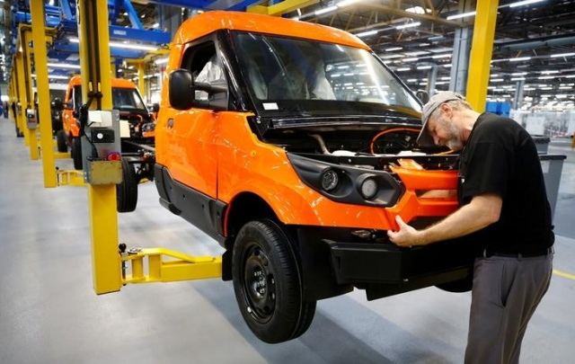 A worker assembles a StreetScooter electric delivery van on the production line during an opening tour in Dueren near Cologne