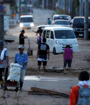 Local residents walk in a flooded area in Mabi town in Kurashiki
