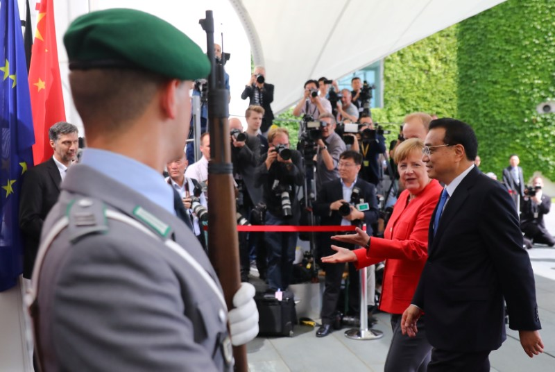 German Chancellor Merkel and Chinese Prime Minister Li Keqiang review the guard of honour at the chancellery in Berlin