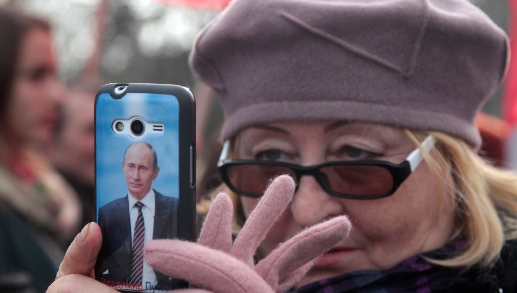 A portrait of Russian President Putin is seen on a cover of a woman's phone as she takes pictures during celebrations of the Russian national holiday - Defender of the Fatherland Day in Sevastopol