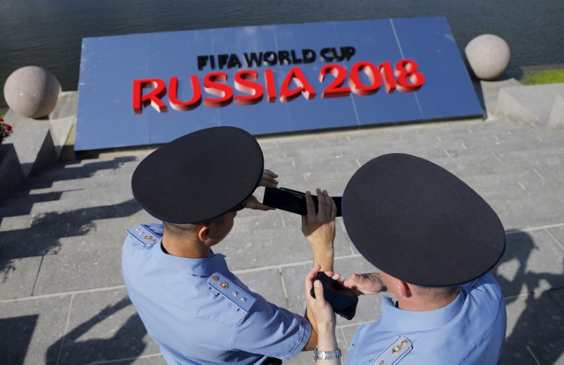 Russian police officers hold their mobile phones as they guard area before preliminary draw for 2018 World Cup in St. Petersburg
