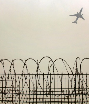 A plane flies in the polluted air above the airport fences in Beijing