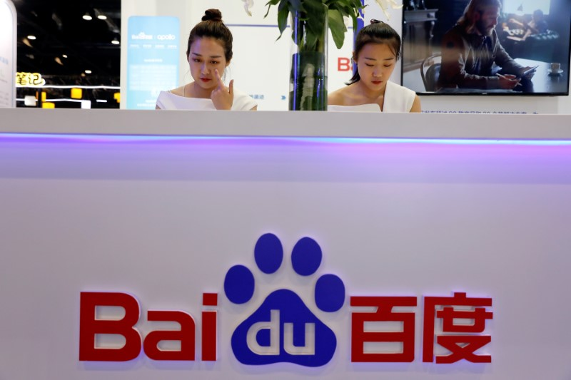Members of staff work at the Baidu booth during Global Mobile Internet Conference (GMIC) at the National Convention in Beijing