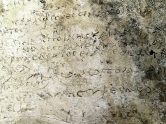 Picture of a clay plaque with an engraved inscription depicting thirteen verses from the Odyssey's 14th Rhapsody