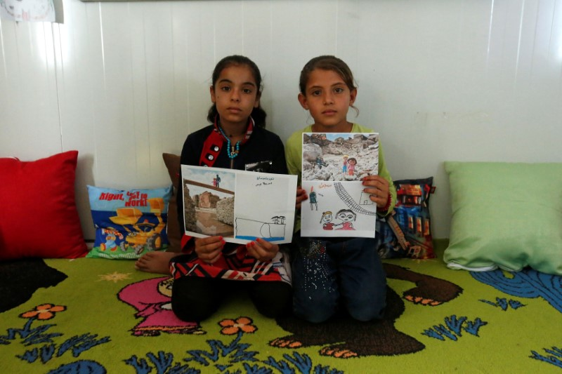 Iraqi refugees pose with their art therapy drawings and renditions by U.S. photographer Brian McCarty at Debaga camp for the displaced on the outskirts of Erbil