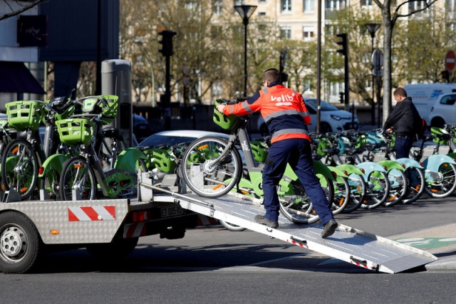 An employee of Velib' Metropole self-service public bike by Smovengo loads a bicycle onto a truck at a distribution point in Paris