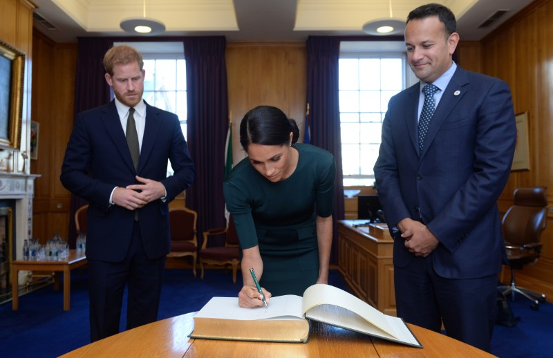 Britain's Prince Harry and his wife Meghan, the Duke and Duchess of Sussex, sign the visitors book in the office of the Taoiseach Leo Varadkar, at the start of a two-day visit to Dublin