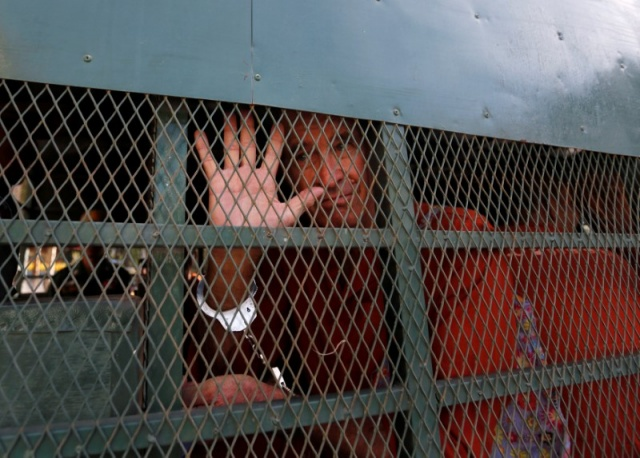Australian filmmaker James Ricketson gestures inside a prison truck as he arrives at the Municipal Court of Phnom Penh