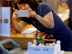 A member of Apple staff takes pictures as new iPhone X begins to sell at an Apple Store in Beijing