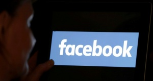 A woman looks at the Facebook logo on an iPad in this photo illustration