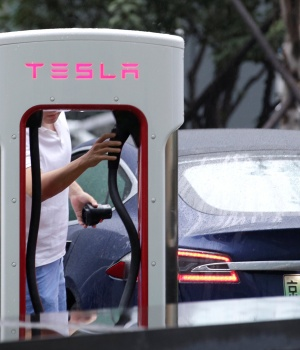 A man finishes to charge his Tesla car at a charging point in Beijing