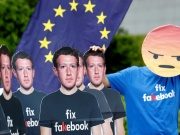 A protester holds an EU flag next to cardboard cutouts depicting Facebook CEO Zuckerberg during a demonstration in Brussels
