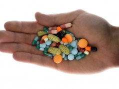 A person holds pharmaceutical tablets and capsules in illustration picture