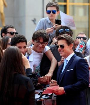 """Cast member Tom Cruise poses for cinema fans as he arrives for the world premiere of """"Mission: Impossible - Fallout"""" in Paris"""