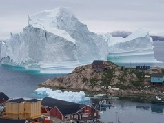 A giant iceberg is seen behind an Innaarsuit settlement