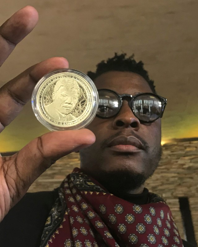 Sindiso Nyoni holds a 1-ounce pure gold 5 rand coin that he designed, as the South African Reserve Bank (SARB) launched a set of limited edition bank notes and gold coins to mark the 100th anniversary of the birth of Nelson Mandela