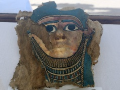 A broken mummy mask is seen inside a glass casing, on display near Egypt's Saqqara necropolis, in Giza