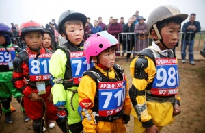 Child jockeys wait in line for a check up before a horse race at the Mongolian traditional Naadam festival, on the outskirts of Ulaanbaatar