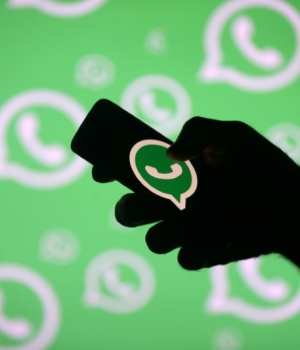 A man poses with a smartphone in front of displayed Whatsapp logo in this illustration