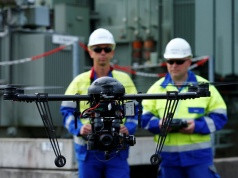 Workers operate a drone to survey high-voltage power lines of electric company Westnetz near Wilnsdorf