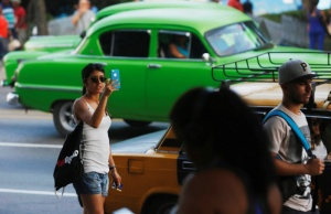 A woman uses the internet on her mobile phone at a hotspot in Havana, Cuba