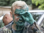 Vitaliy Shabunin, head of the non-governmental Anti-Corruption Action Centre, reacts after he was splashed with brilliant green substance during a rally in Kiev