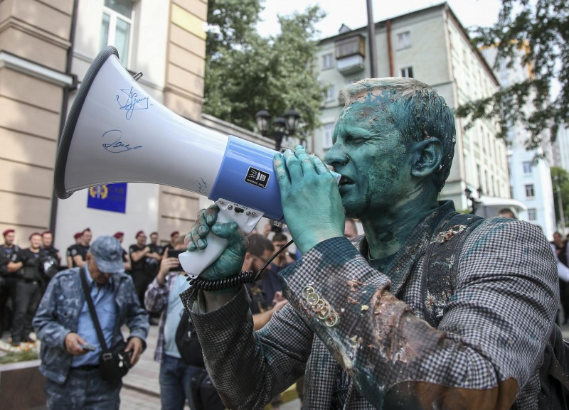 Head of the non-governmental Anti-Corruption Action Centre Vitaliy Shabunin, who was splashed with brilliant green substance, uses a loud-speaker during a rally in Kiev