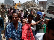 People carry a woman, whose husband is trapped under the rubble, after she got fainted at the site of a collapsed residential building at Shah Beri village in Greater Noida