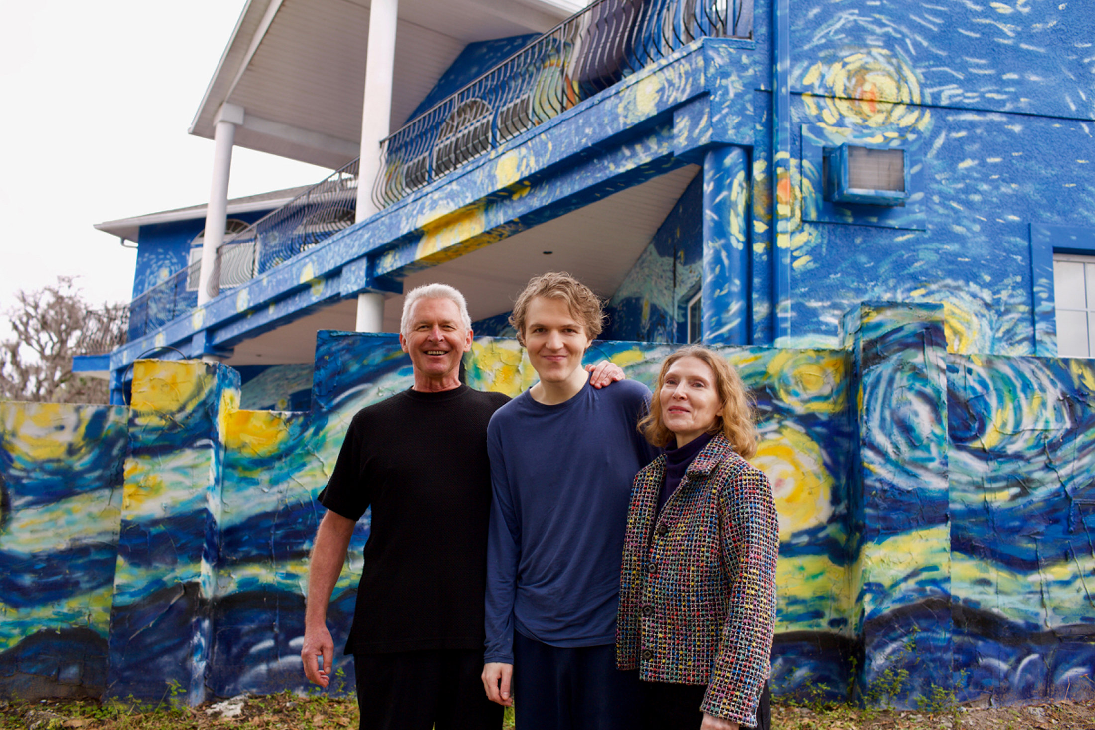 Lubomir Jastrzebski and Nancy Nembhauser pose with their adult son in front of the house in Mount Dora, Florida